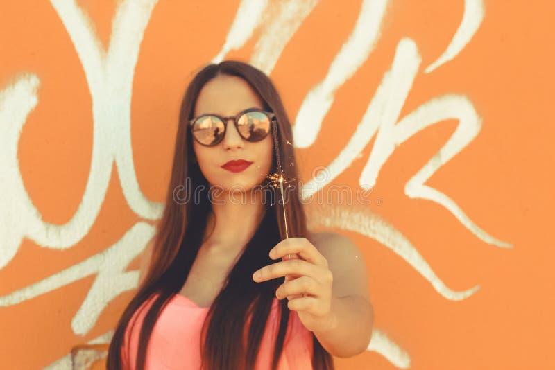 Ung flicka som rymmer ett tomtebloss och bär trendig solglasögon royaltyfri bild