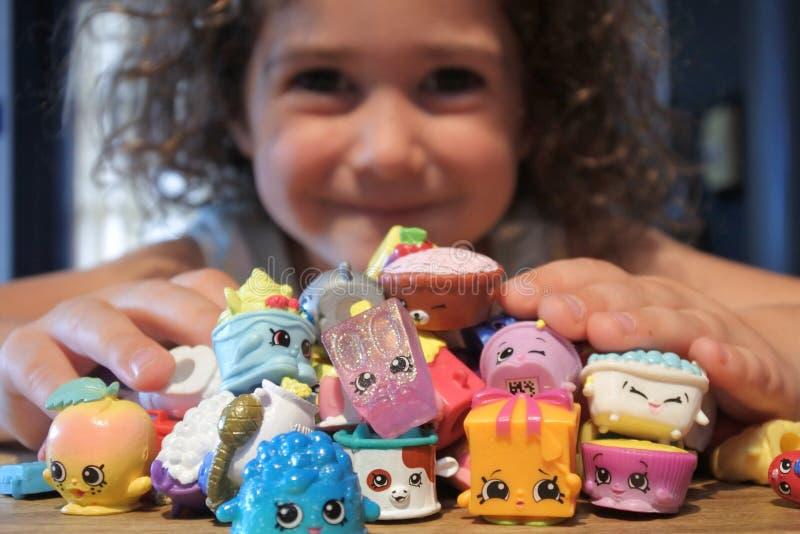 Ung flicka som rymmer Shopkins ett omr?de av mycket sm? collectible leksaker som tillverkas av ?lgleksaker arkivbild