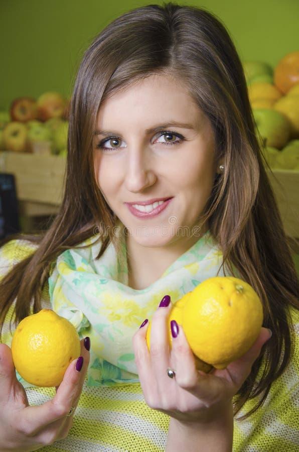 Ung flicka som rymmer två citroner i greengrocery royaltyfria bilder