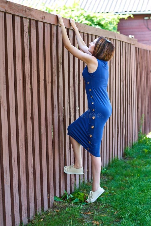 Ung flicka som ser över staketet och har gyckel royaltyfria bilder
