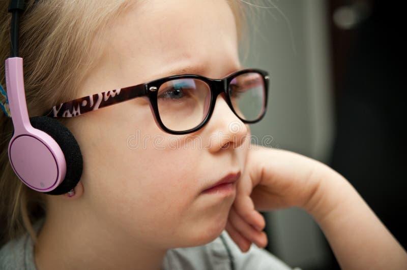 Ung flicka som ser bärbar datorskärmen royaltyfri foto