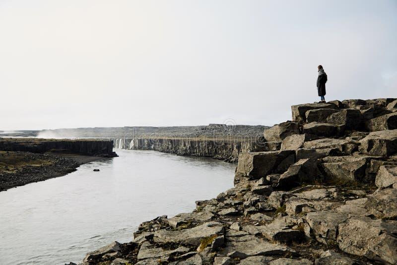Ung flicka som ser landskapet Hon beundrar naturen av Island arkivfoto