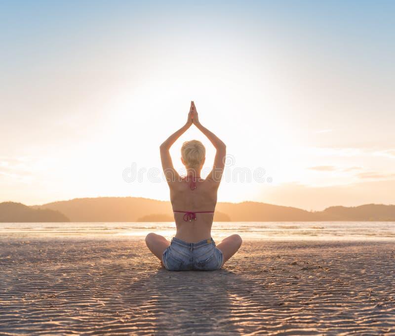 Ung flicka som sitter den Lotus Pose On Beach At solnedgången, för yogasommar för härlig kvinna praktiserande sjösida för meditat arkivfoton