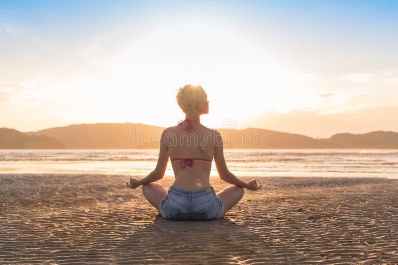 Ung flicka som sitter den Lotus Pose On Beach At solnedgången, för yogasommar för härlig kvinna praktiserande sjösida för meditat arkivfoto