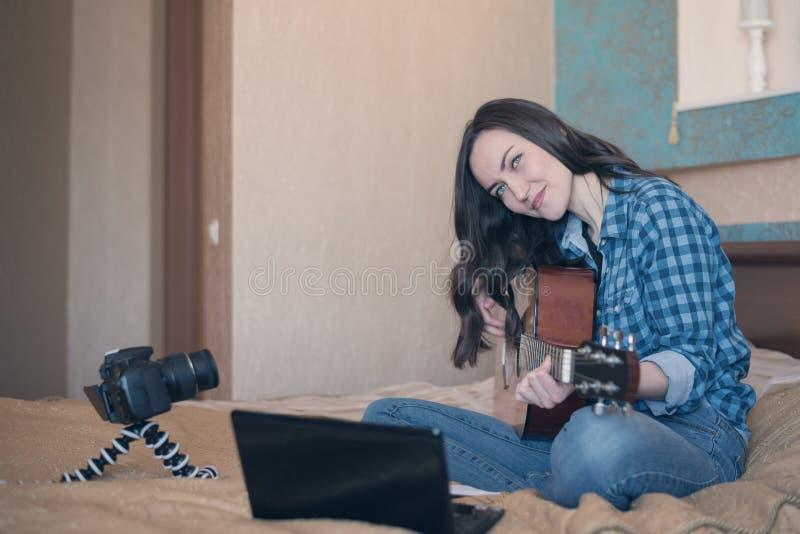 Ung flicka som spelar den akustiska gitarren i rummet royaltyfri fotografi