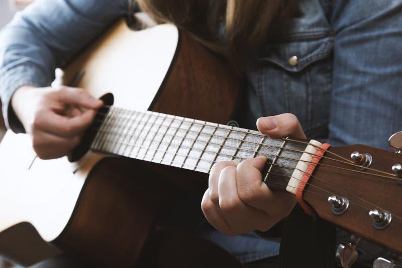 Ung flicka som spelar den akustiska gitarren med jeansskjortan royaltyfri bild