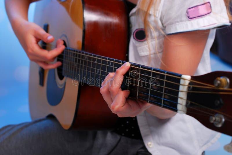 Ung flicka som spelar den akustiska gitarren på etappen arkivbilder