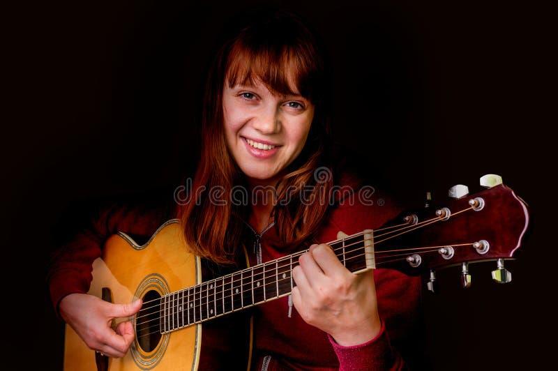 Ung flicka som spelar den akustiska gitarren - på svart arkivbilder
