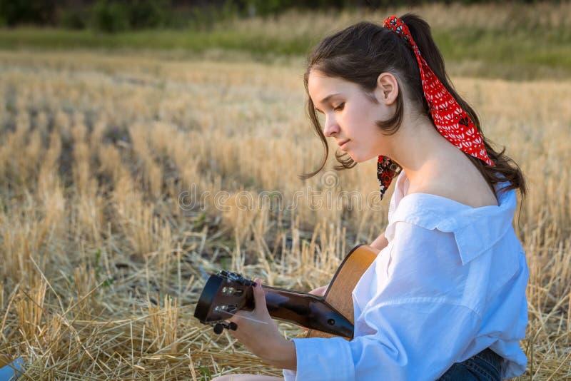 Ung flicka som spelar gitarr på halmfältet royaltyfria foton