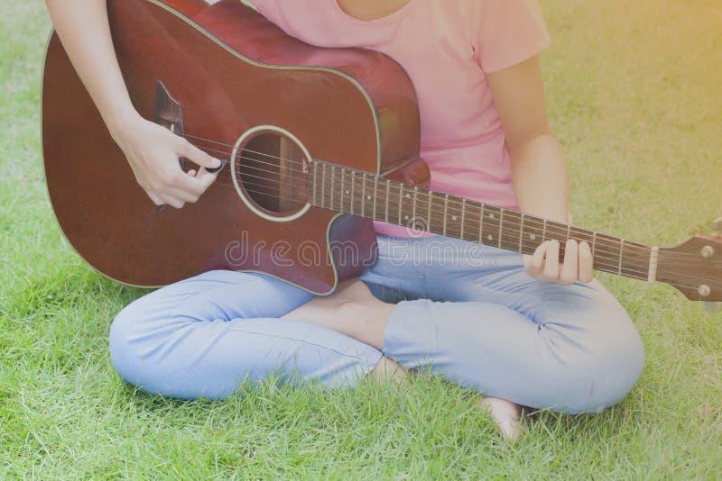 Ung flicka som spelar gitarren, solnedgångtappningsignal royaltyfri fotografi