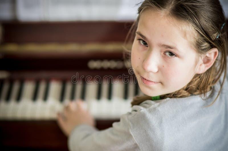 Ung flicka som spelar på piano royaltyfri bild