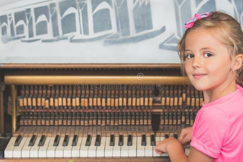 Ung flicka som spelar på pianot arkivbilder