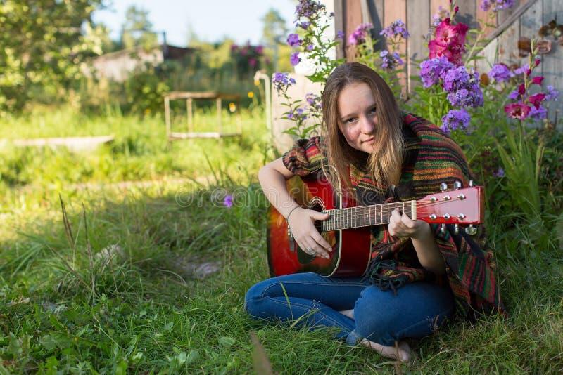Ung flicka som spelar sammanträde för akustisk gitarr utomhus hippie arkivbilder
