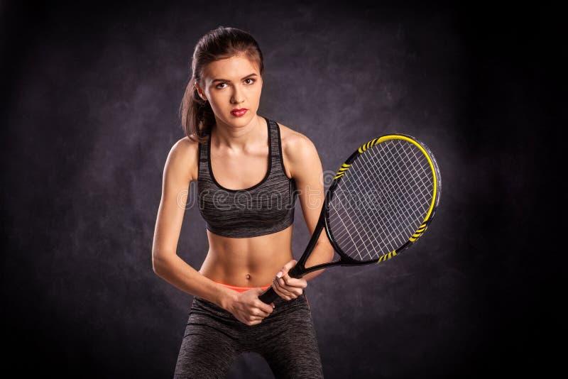 Ung flicka som spelar tennis med racket arkivfoton