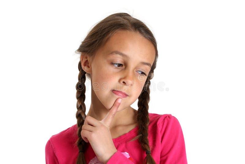 Ung flicka som tänker med hennes finger på hennes haka fotografering för bildbyråer