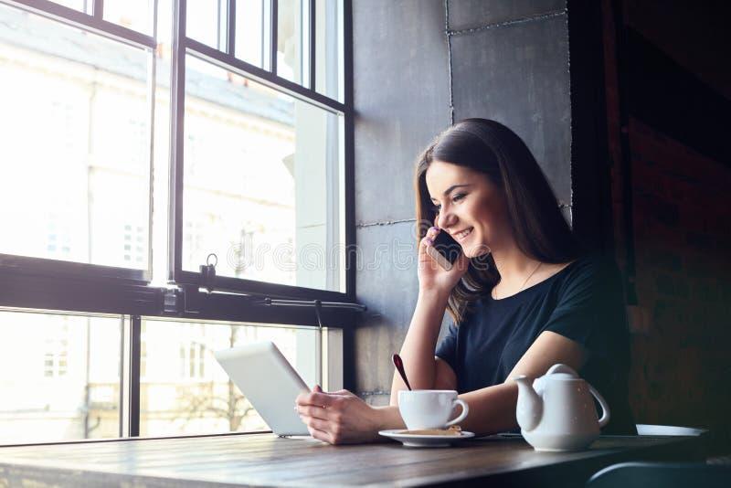 Ung flicka som talar på mobiltelefonen i coffee shop royaltyfri fotografi