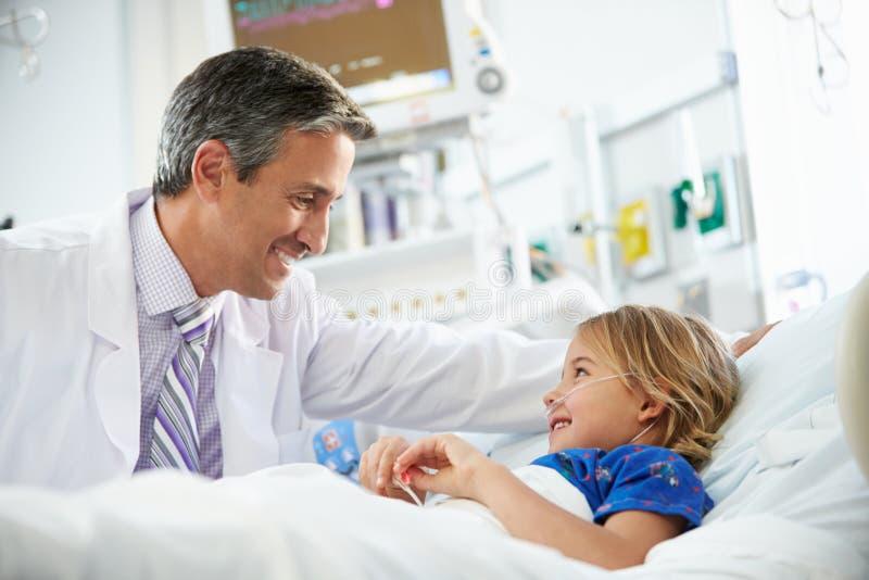Ung flicka som talar till den manliga enheten för doktor In Intensive Care arkivfoton