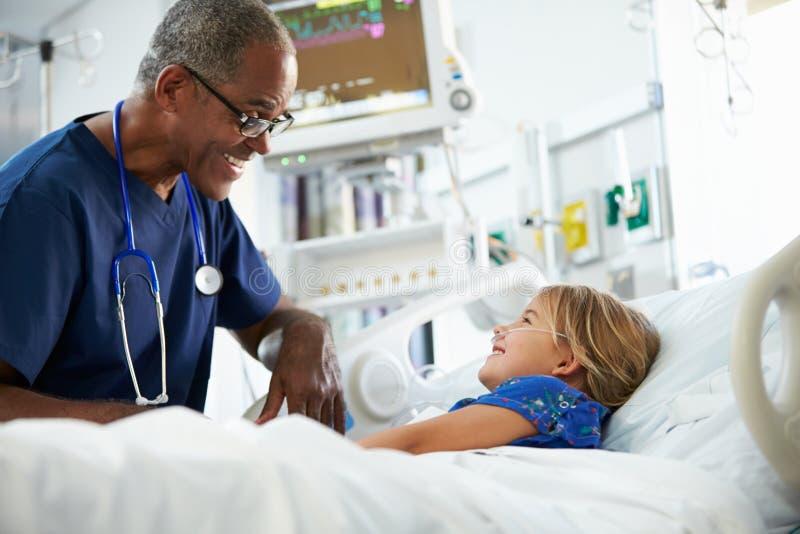 Ung flicka som talar till den sjukskötareIn Intensive Care enheten arkivfoto
