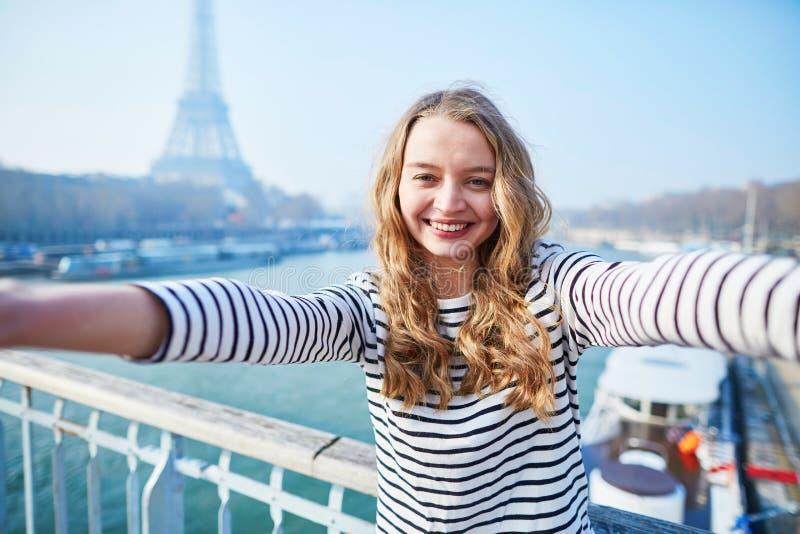 Ung flicka som tar selfie nära Eiffeltorn royaltyfri bild