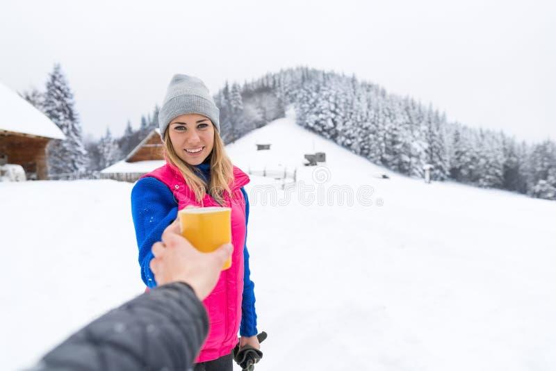 Ung flicka som tar varmt kaffe eller te för kopp trästuga för semesterort för snö för vinter för landshus arkivfoton