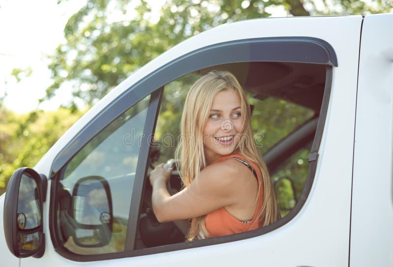Ung flicka som tillbaka på ser från bilfönster arkivbild