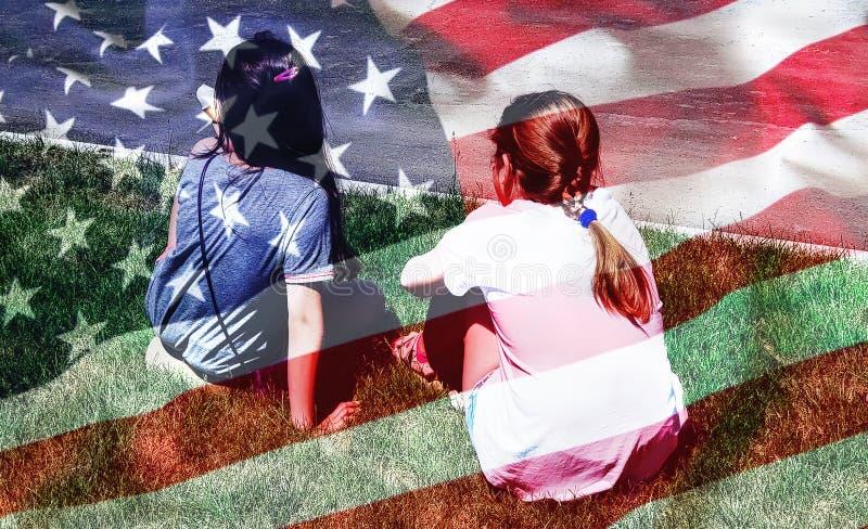 Ung flicka som två slås in i amerikanska flaggan retro självständighet för bakgrundsdaggrunge arkivfoto