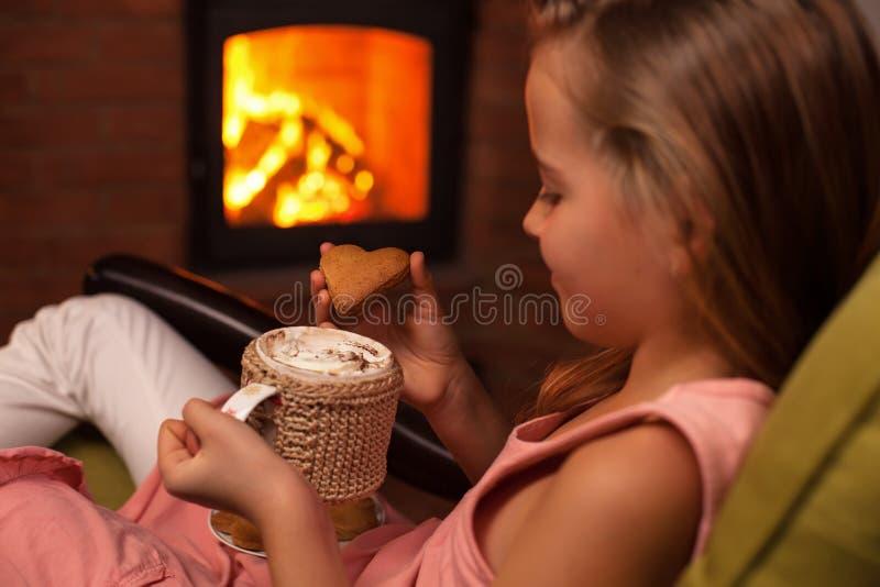 Ung flicka som tycker om en kaka med en varm choklad som sitter vid arkivbild