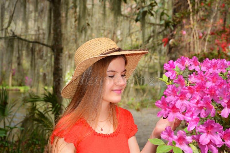 Ung flicka som tycker om tid i den härliga blommande trädgården fotografering för bildbyråer