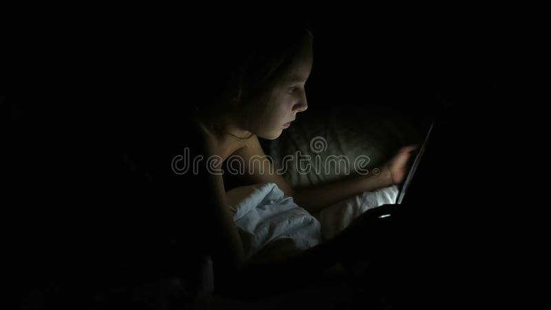 Ung flicka som ut skrattar och klibbar hennes tunga Ung caucasian kvinnlig lycklig flicka i säng på natten med minnestavlaläsning royaltyfria bilder