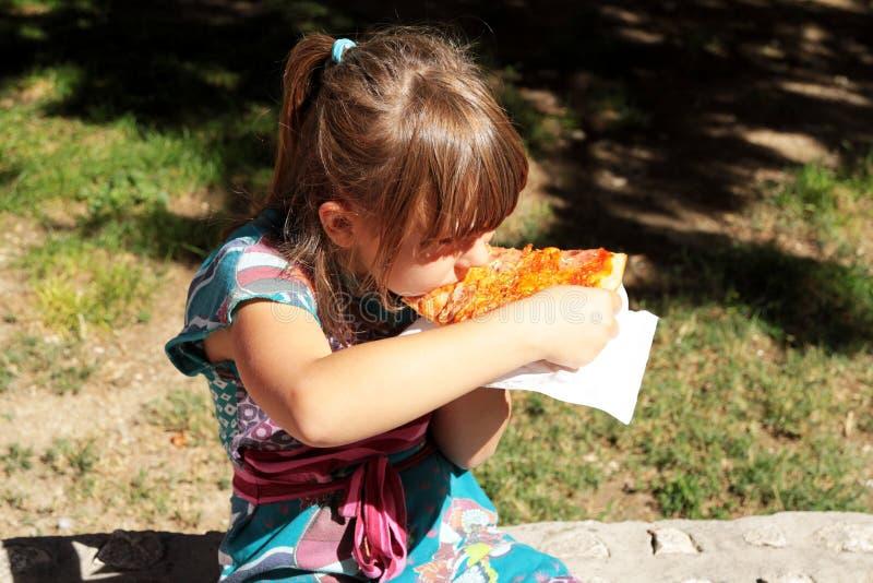 Ung flicka som utanför äter en skiva av ostpizza royaltyfria foton