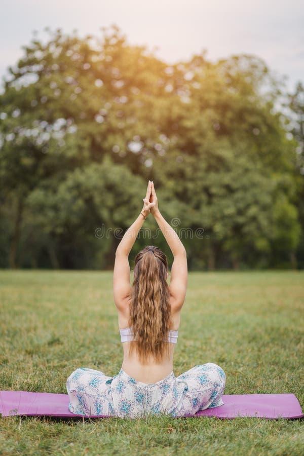 Ung flicka som utomhus gör yoga arkivfoton
