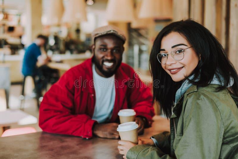 Ung flicka som vänder och ser dig, medan sitta med hennes pojkvän royaltyfria foton