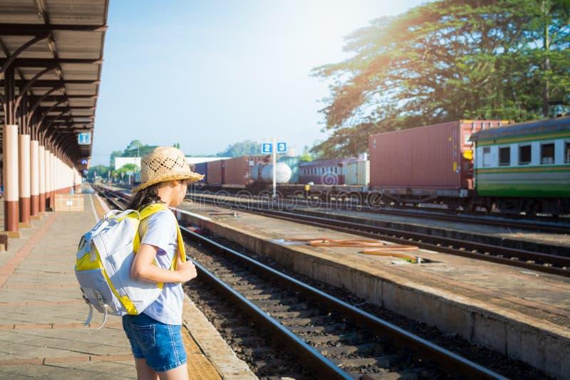 Ung flicka som väntar på ett drev på järnvägsstationen royaltyfri fotografi