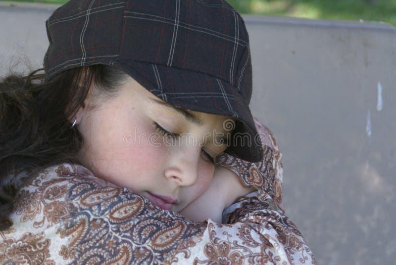Ung flicka som vilar på parkbänk arkivfoto