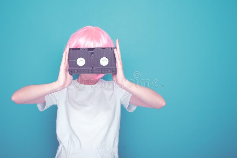 Ung flicka90-tal och VHS kassett på royaltyfri bild