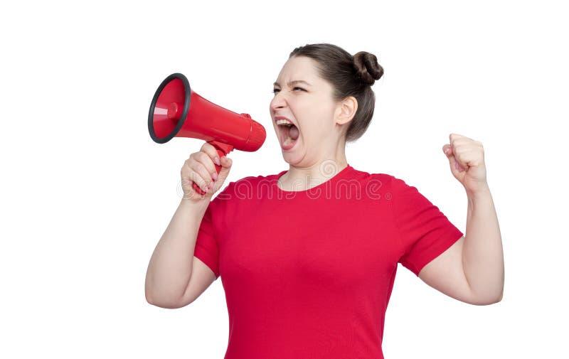 Ung flickaaktivist i en röd t-skjorta som skriker in i en megafon som isoleras på vit bakgrund royaltyfri bild