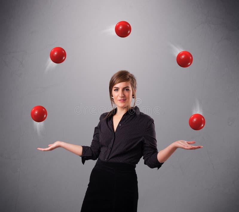 Ung flickaanseende och jonglera med röda bollar royaltyfri bild