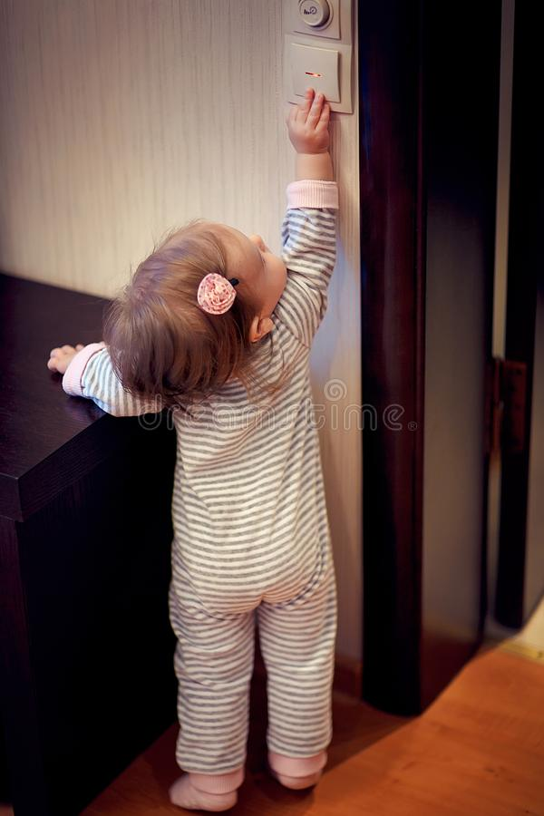 Ung flickaanseende och rörande strömbrytare royaltyfria foton