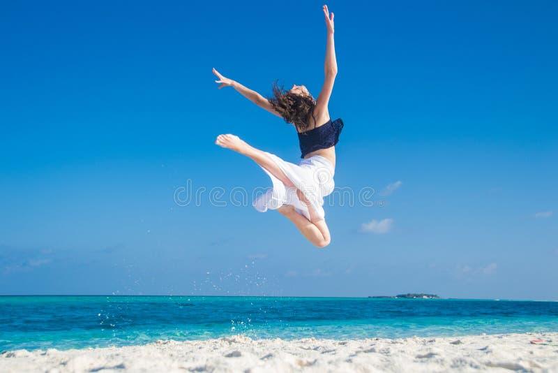 Ung flickabanhoppning på den tropiska stranden royaltyfria bilder