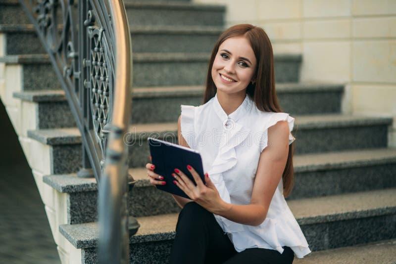 Ung flickabruk en minnestavla och en telefon att arbeta Flickan i kafét ler royaltyfri bild