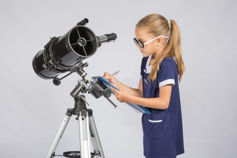 Ung flickaexponeringsglas skriver astronomobservationer royaltyfri bild