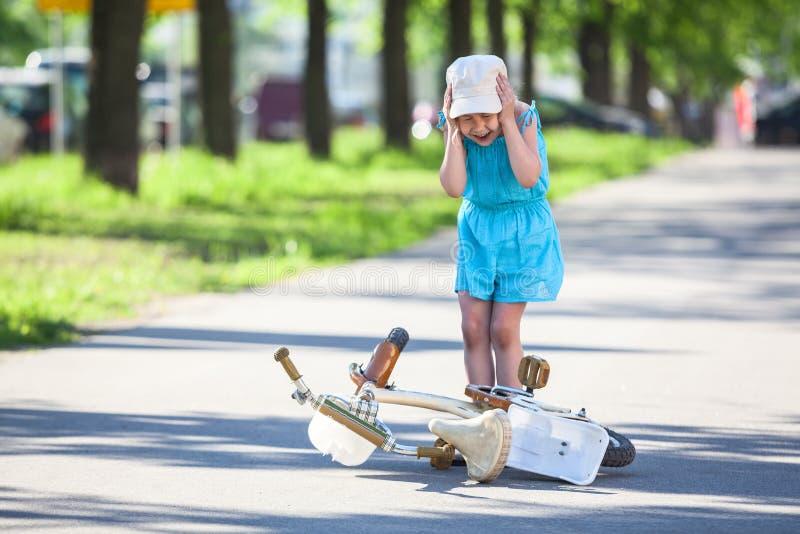 Ung flickagråt, når att ha fallit ner från cykeln royaltyfri bild