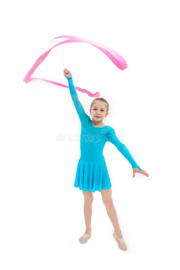 Ung flickagymnast som övar med det rosa bandet på vit arkivbild
