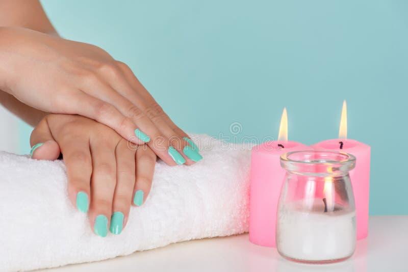 Ung flickahänder med en turkosfärg spikar polermedel på handduken och dekorativa rosa stearinljus på skrivbordet royaltyfria foton