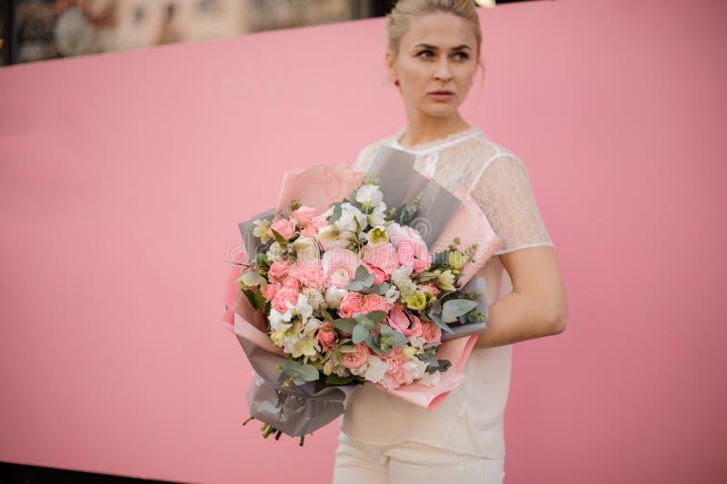 Ung flickahållbukett i grått och rosa papper royaltyfri bild