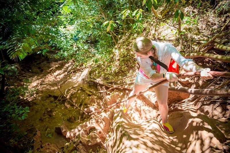 Ung flickahandelsresande i vita klättringar berget på ett rep Top besk?dar Tropisk djungel omkring arkivbilder