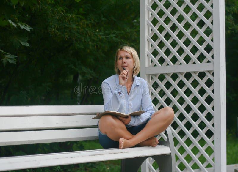 Ung flickahandstil i hennes anteckningsbok på parkerar på bänk royaltyfri foto