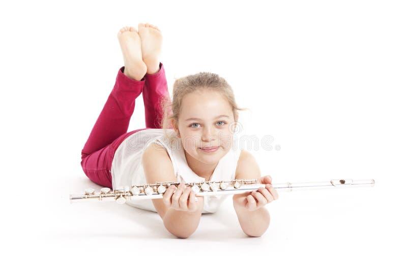 Ung flickainnehavflöjt som ligger på golvet arkivbild