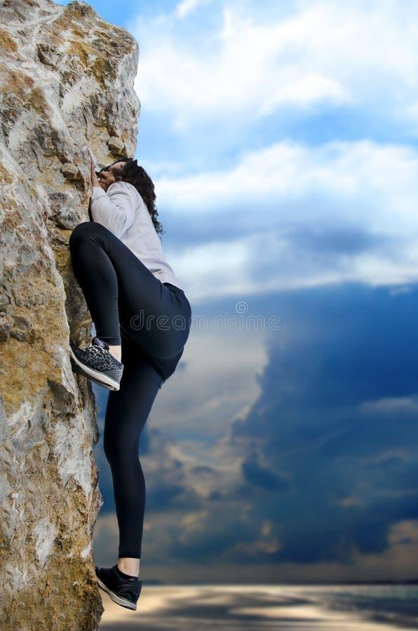 Ung flickaklättring på en kalkstenvägg arkivfoton