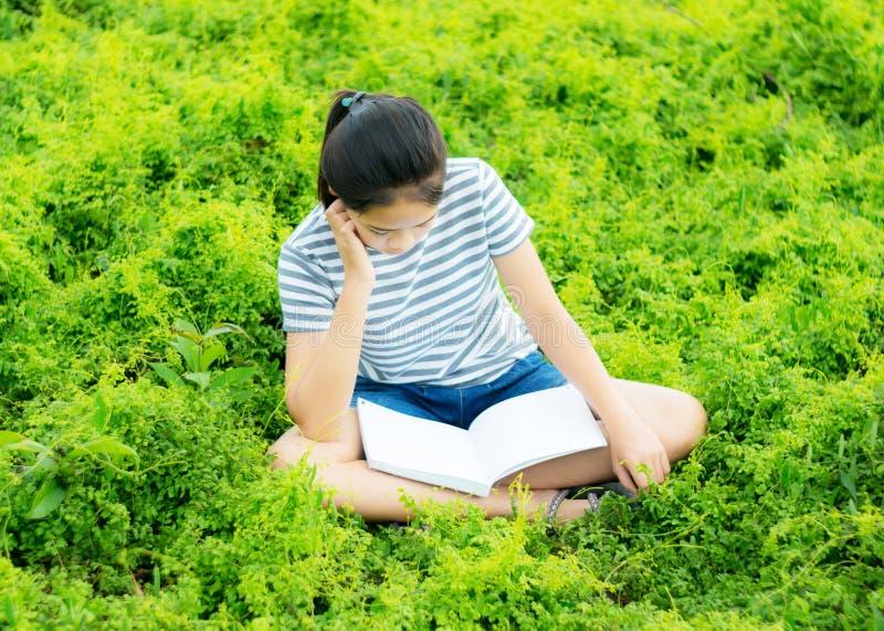 Ung flickaläsning i grön ängcontrysidenatur fotografering för bildbyråer